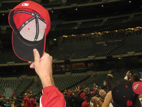 A St. Louis Cardinals fan raising his hat in triumph to celebrate the Cardinals' National League Championship Series win over the Millwaukee Brewers on Oct. 16, 2011.