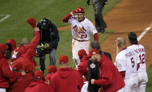 Cardinals David Freese celebrates with his teammates at home plate after hitting a solo walk off homerun to win game 6 of the World Series in the 11th inning against the Texas Rangers in St. Louis on October 27, 2011.