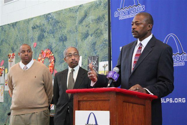 Michael Lidell (L) and attorney William Douthit (C) watch as Supt. Kelvin Adams announces an agreement that allows the SLPS to use $96 million from the settlement of a desegregation lawsuit to pay off debt and fund education initiatives.