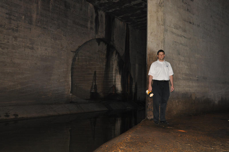 MSD spokesperson Lance LeComb stands next to one of the 29-foot diameter combined sewer tunnels that run under Forest Park. Raw sewage can be seen flowing by.