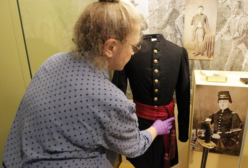 Missouri History Museum employee Shery Hunter perfects the installation of a Union uniform.