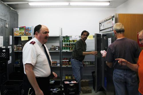 Captain Paul Ferguson (left) directs volunteers during a weekly food pickup day at the Salvation Army's food pantry in O'Fallon, Mo. The food pantry has seen a ten-fold increase this year alone.