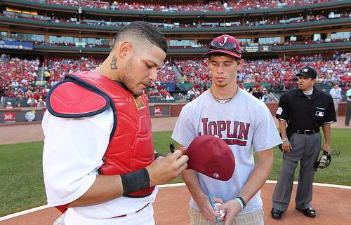 St. Louis Cardinals catcher Yadier Molina signs an autograph for Joplin High School baseball player Tyler Russell before a game against the Kansas City Royals at Busch Stadium in St. Louis on June 18, 2011.