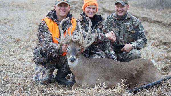 Deer hunters display their unusual find - a female deer with developed antlers.