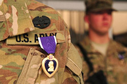 A Purple Heart medal and combat field medic badge is pinned on the chest of U.S. Army Spc. Tamara Becker during a ceremony in Kabul, Afghanistan, Oct. 30, 2011.
