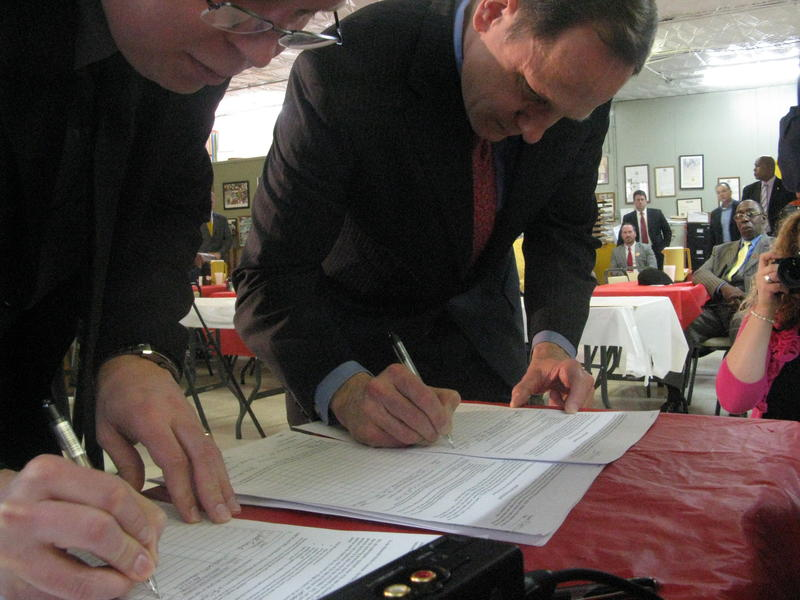 Jeff Roorda, business manager for the St. Louis Police Officers Association (left), and St. Louis Mayor Francis Slay sign petitions to let voters decide whether St. Louis should control its own police department.