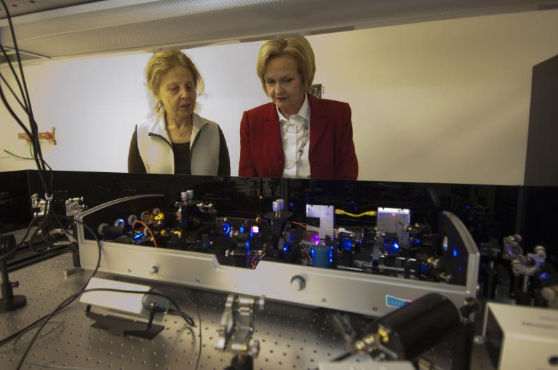 Senator Claire McCaskill (at right) takes a look at an ultrafast laser system with Christine Kirmaier, PhD, (at left) research professor of chemistry, at Washington University in St. Louis' Ultrafast Laser Facility.