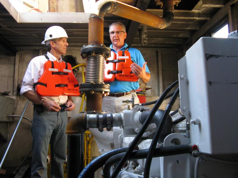 EPA Regional Administrator Karl Brooks (left) and JB Marine Service, Inc., CFO David Heyl talk in the engine room of the tugboat Helen Virginia. In the foreground is one of the new, lower-emission engines.