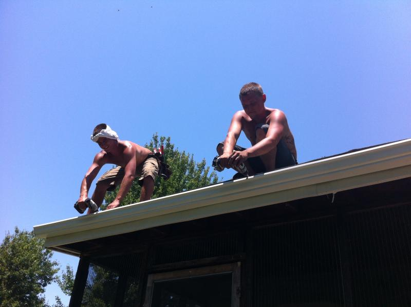 Workers installing a rain gutter in the heat.