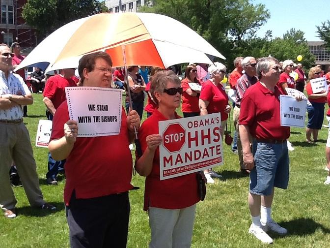 Rally participants hold signs expressing their opposition to the president's contraceptive mandate.