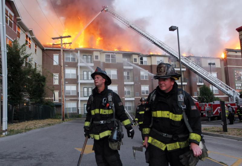 St. Louis firefighters work to contain a fire on the roof of an apartment building during a five alarm fire in St. Louis on July 17, 2012. Nearly 200 apartments in the complex were involved after a fire spread throughout the roof of the buildings.