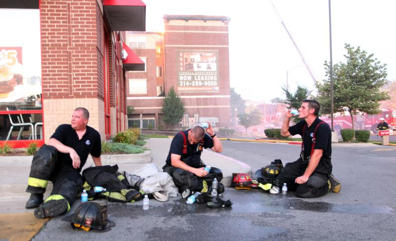 Firefighters try to stay cool while battling a five-alarm blaze at 3949 Lindell Blvd, near Lindell and Vandeventer. Two firefighters were treated for heat exhaustion while working in 90+ degree temperatures.