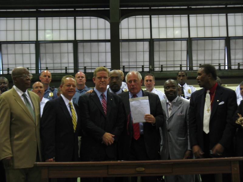 Ill. Gov. Pat Quinn (holding paper, center) poses for a photograph with representatives from several Metro East police departments and municipalities on Aug. 16, 2012.