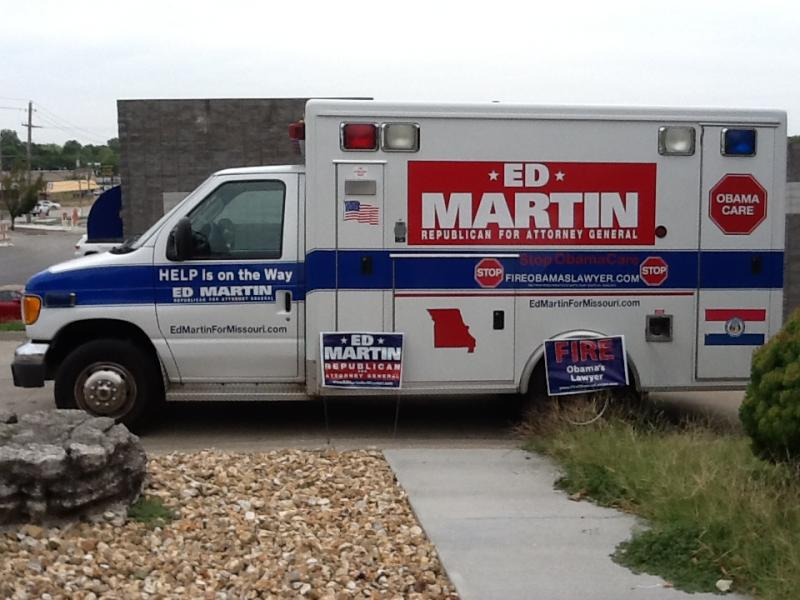 A decommissioned ambulance being used by Ed Martin's campaign sits parked near the GOP tour bus.