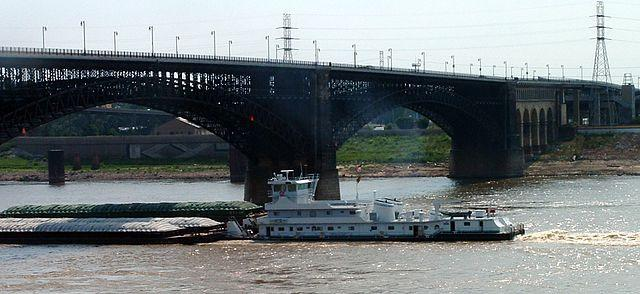 A tugboat pushes a barge under the Eads Bridge in St. Louis