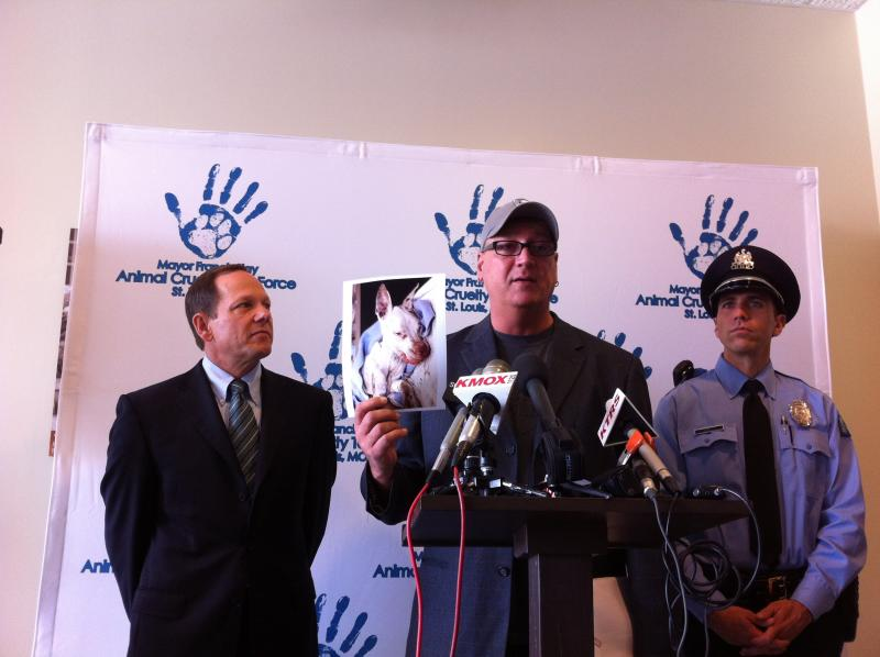 Stray Rescue's Randy Grim holds up a picture of a tortured dog. At left, St. Louis Mayor Francis Slay and at right, Officer Louis Naes.