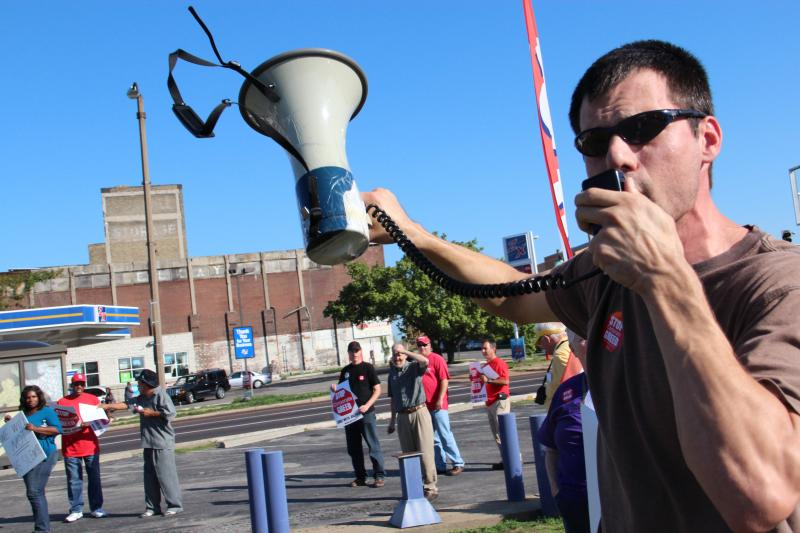 Justin Stein of Jobs with Justice leads protesters outside a payday loan shop on Grand Ave. on Wednesday, Sept. 5.