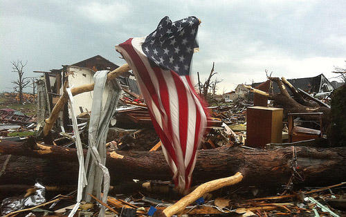 An American flag blows in the wind, attached to a downed limb, near a home that has been destroyed in Joplin, Missouri on May 23, 2011. A massive tornado hit the small southwestern Missouri town on May 22, 2011.