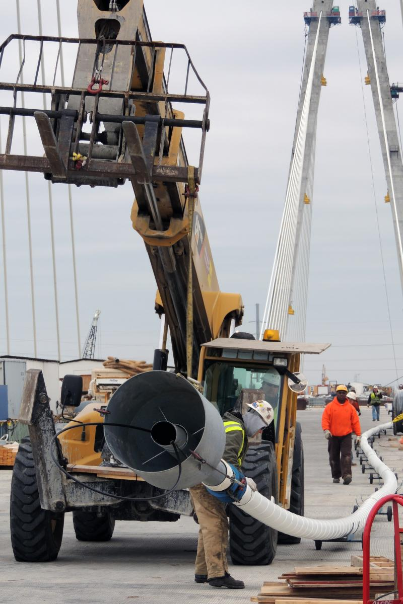 Workers move a new conduit into position.