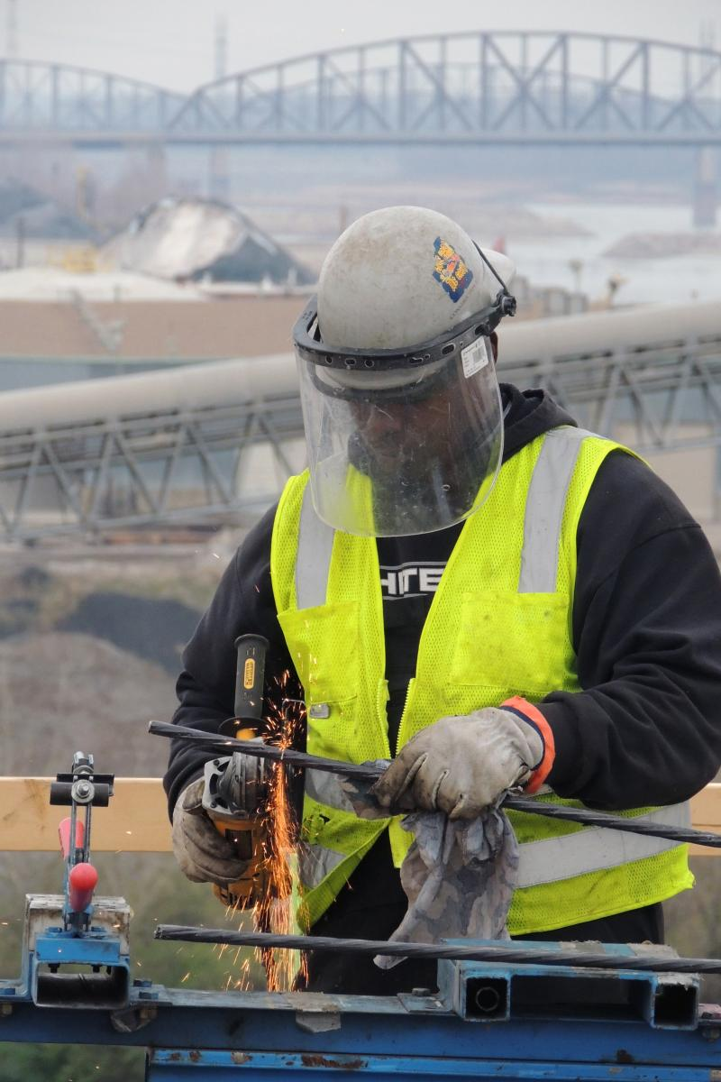 A closer look at a worker preparing a cable for installation.