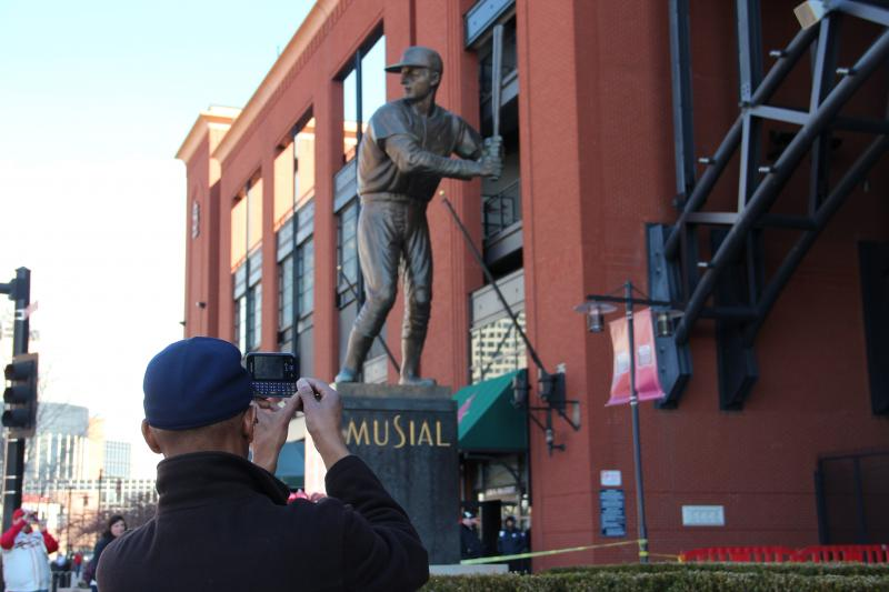 A fan uses his cell phone to snap a picture of the statue of Stan Musial at the entrance to Busch Stadium on Sunday, Jan. 20, 2013