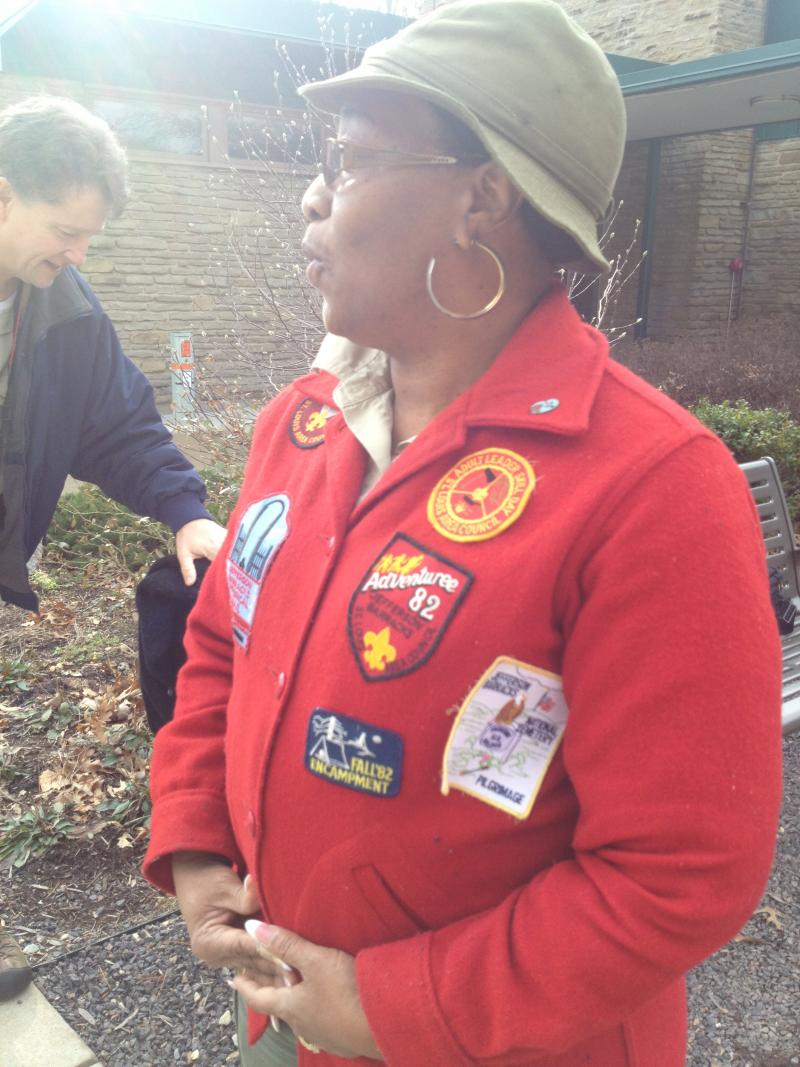 Scoutmaster Hall's sweater is donned with various badges representing her involvement with the Boy Scouts.