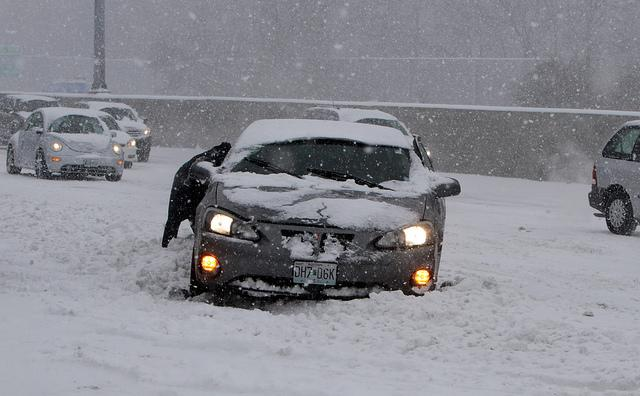 A motorist is helped after encountering a snow drift on Highway 64 in Ladue, Mo. on February 21, 2013.