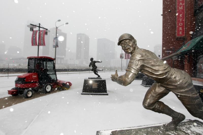 Snowflakes fall around the Lou Brock statue as Busch Stadium workers begin to clear the area in St. Louis on February 21, 2013. A morning ice storm and then several inches of snow have slowed or closed roads, businesses and schools.