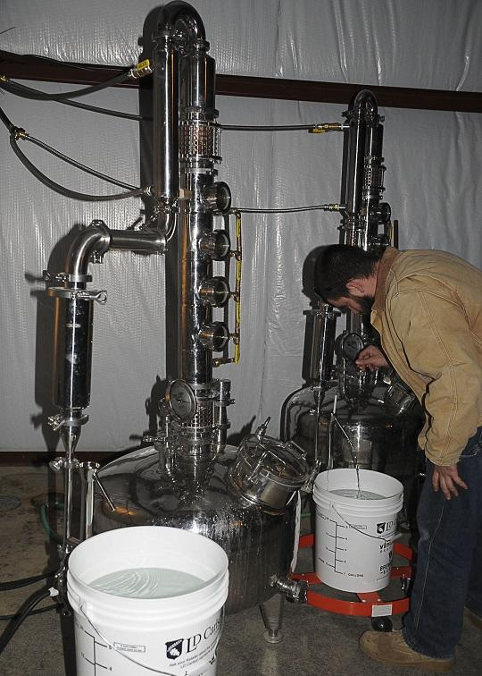 Chris Burnette, Pres. of Mad Buffalo Distillery, adjusts one of the stills used to make white whiskey, a.k.a. moonshine.