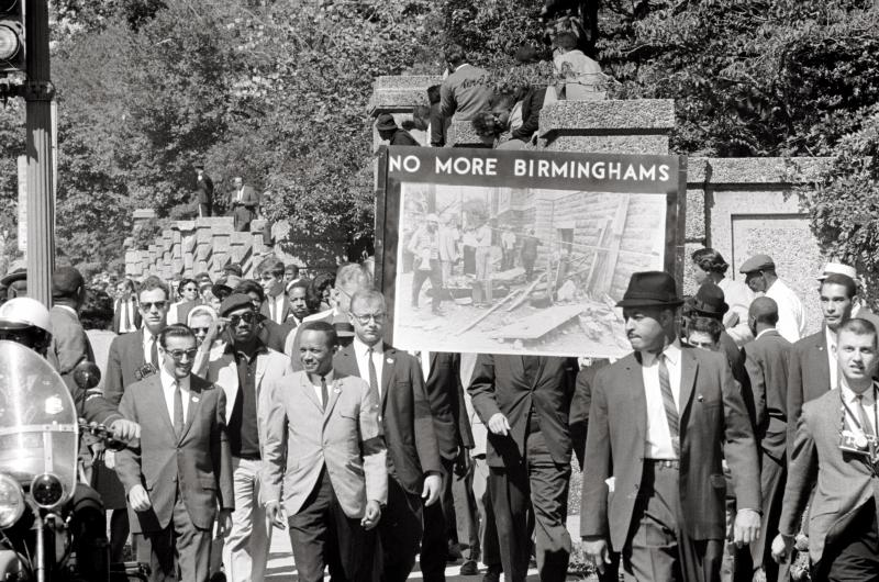 "Congress of Racial Equality and members of the All Souls Church, Unitarian in Washington, D.C. march in memory of the 16th Street Baptist Church bombing victims. The banner, which says ""No more Birminghams"", shows a picture of the aftermath of th"