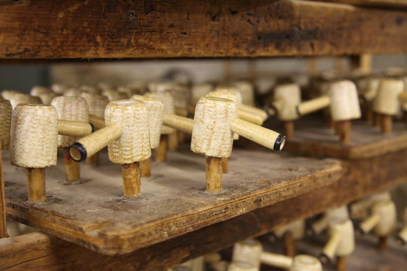 Having been dried, shaped and plastered, pipes await the finishing touch at the Missouri Meerschaum Co. Located in Washington, Mo. it's the world's only mass manufacturer of authentic corn cob pipes.