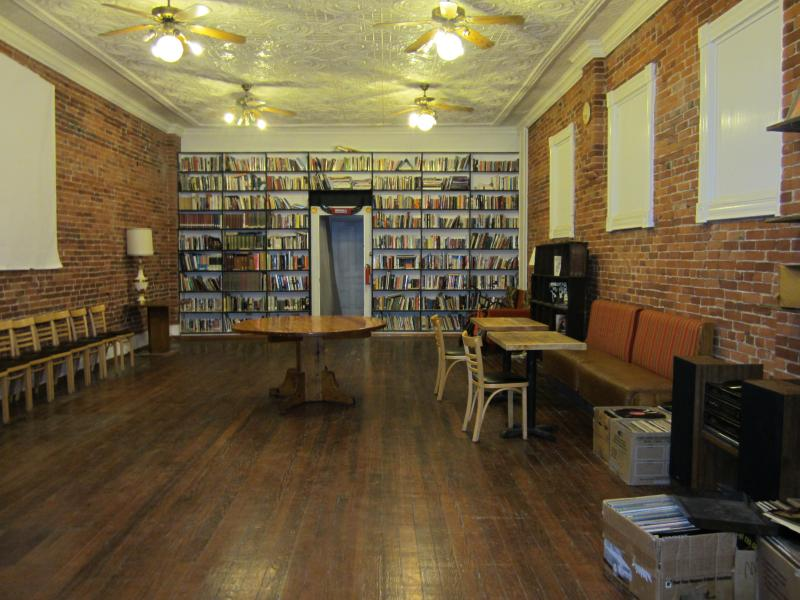 The mostly sparse main floor of Blank Space is lined with a wall of books on the opposite end.