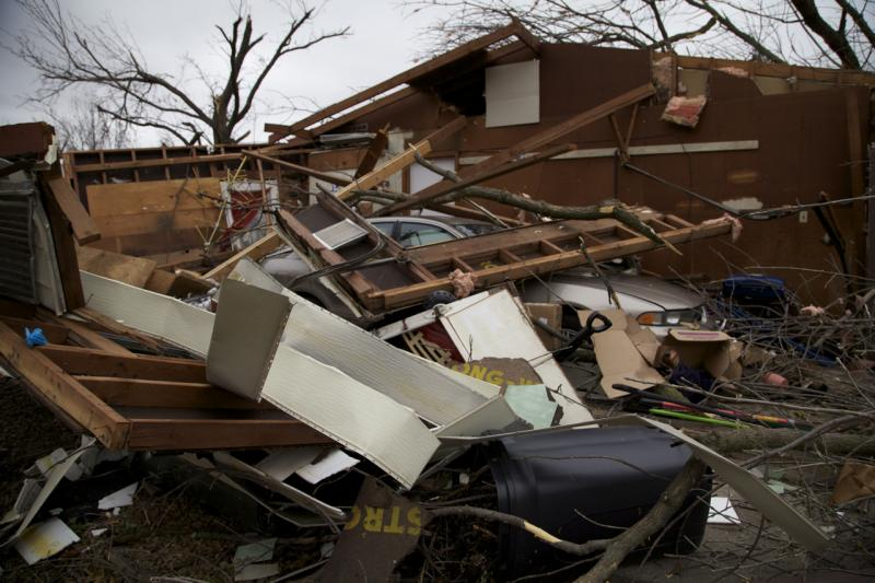 A car sits beneath piles of storm debris.