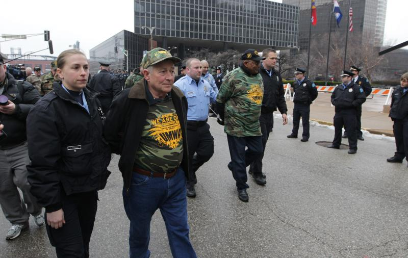 Police walk arrested mine workers to a police van Feb. 26 after they refused an order to get out of the street during a rally outside of the Peabody Energy Company headquarters in St. Louis. Ten people were arrested.
