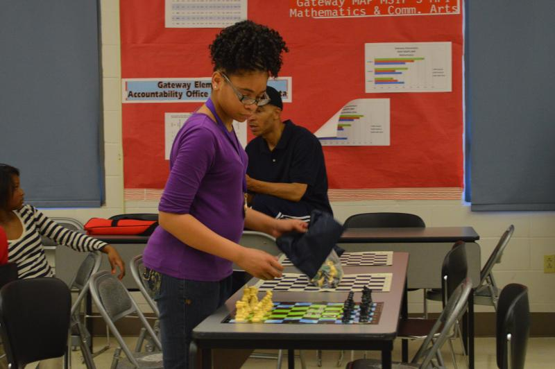 Shakoor sets up a chess board while her father, Abdul, talks with a group of young women who have stayed after school to learn chess. The Shakoors have instructed students at Gateway Elementary over the course of the school year.