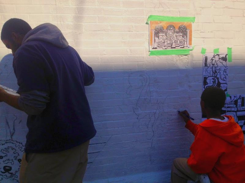 Students begin sketching the chess images on the walls. The mural itself should take between three and four weeks to complete, says McCammond.