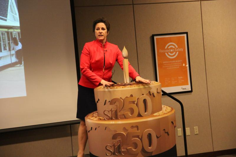 stl250 Executive Director Erin Budde stands next to an example of an ornamental cake