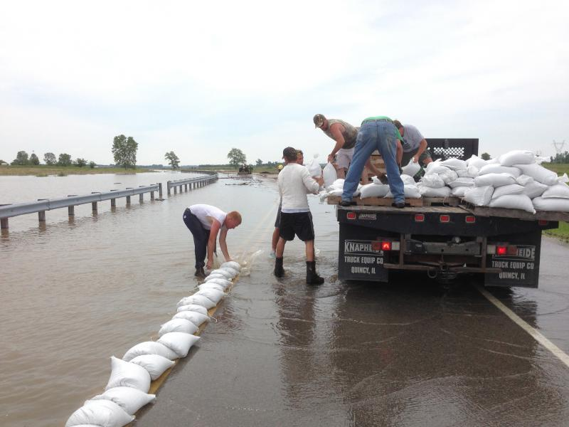 Volunteers try to fight against flooding at Riverlands Way in West Alton, Mo. on June 4, 2013.