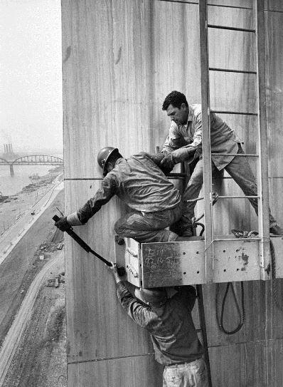 Workers tightening a bolt to secure the creeper derrick platform on the Gateway Arch.