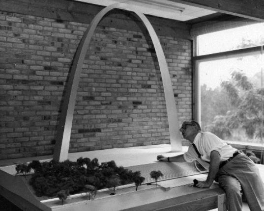 Eero Saarinen under a model of the Gateway Arch in 1957.