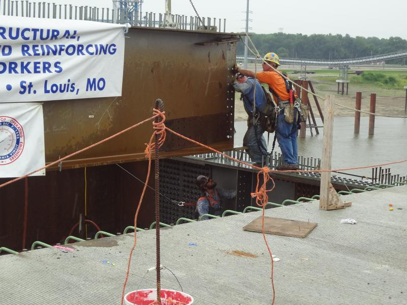 Members of Ironworkers Local 396 maneuver the final steel girder into place on the Stan Musial Veteran's Memorial Bridge on July 26, 2013.