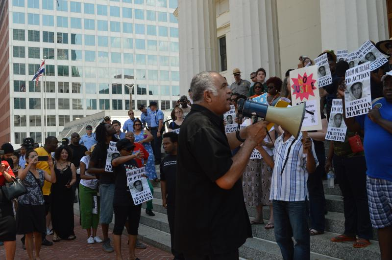 Protestors chanted and held signs while Zaki Baruti offered words of action.