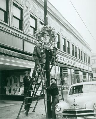 Hanging the holiday decorations, circa 1940.