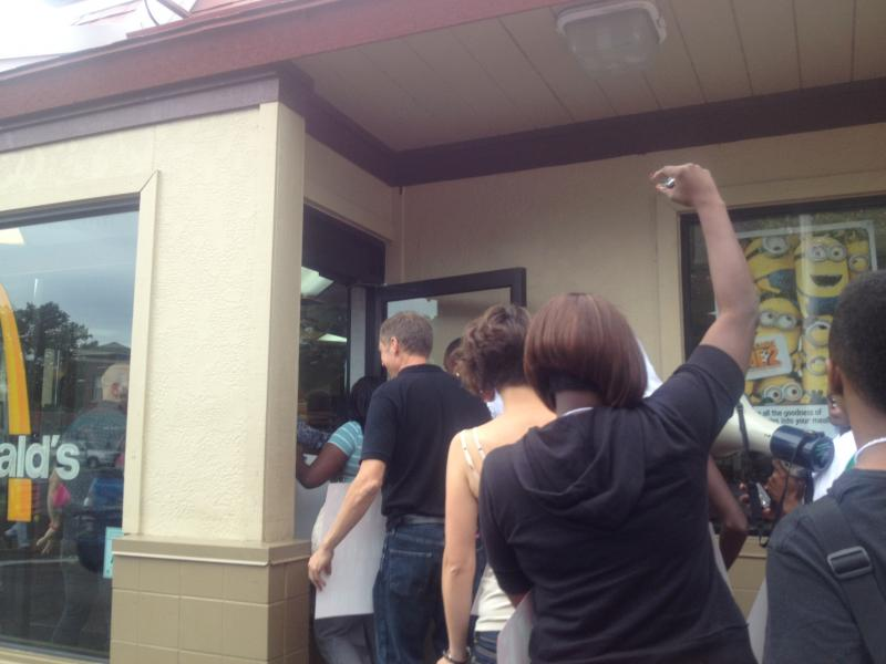 Protestors rush into the McDonald's to chant and protest.