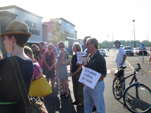 Opponents of a proposed new road through portions of South County listen to speakers at an event on July 16, 2013. They are in the parking lot of Deer Creek Center, which will be impacted by the proposed connector.