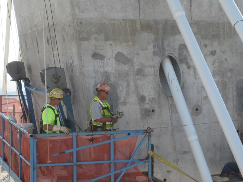 Workers perched about two-thirds of the way up the Missouri-side tower apply patches to the concrete on the new bridge.