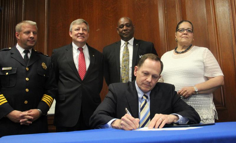 St. Louis Mayor Francis Slay signs an executive order accepting local control of the city's police department.