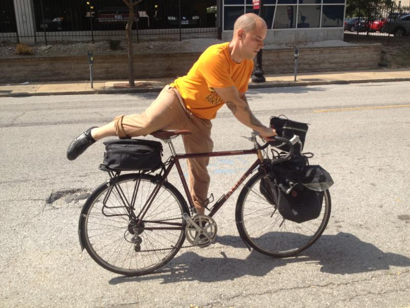 Sean Lowery demonstrates mounting his 1983 Raleigh Olympian bicycle. It has fenders and front and rear racks for transporting groceries. For his daily commute he uses a 1973 fixed-gear Schwinn Varsity.