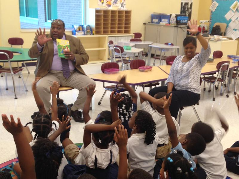 Superintendent Tyrone McNichols reads to kindergarten students at Barack Obama Elementary School. The teacher, Ms. Deidre Sealey, participates in the activity