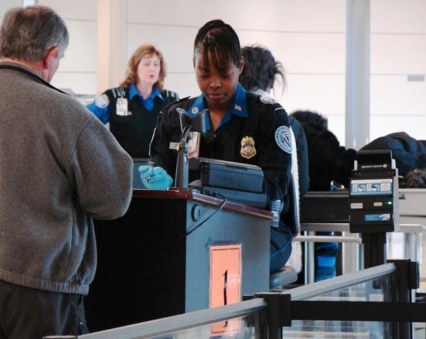 A TSA agent screens a passenger at one of Lambert Airport's PreCheck security lines.